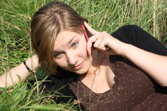 Phoning. Young woman is phoning in the grass Royalty Free Stock Image
