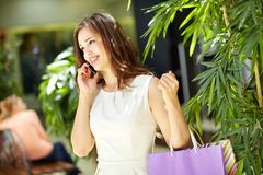 Phoning from mall. Lovely shopping girl talking on the phone in mall Stock Photos