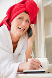 Phoning pampered woman. Scenic scene of red towel pampered woman while phoning and putting notes at home on cupboard Royalty Free Stock Image