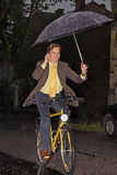 Phoning in the rain. Smiling young man riding a yellow bicycle and phoning in the rain under an umbrella Royalty Free Stock Image