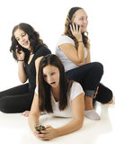 Phoning Teens. Three young teens relaxed together as they each communicate on their phones.  On a white background.  Focus on the girl on the floor Stock Photos