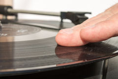 Phonograph Turntable with hand on the vinyl disk Royalty Free Stock Photography