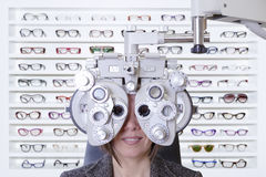 Phoropter and glasses. Closeup of eyesight measurement to a young woman with a phoropter with an exhibitor of fashionable glasses at the background Royalty Free Stock Image