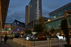 Phosphoreszierende Rotwild, die um den Weihnachtsbaum installiert in Einkaufszentrenspielplatz Westfield Stratford City gehen stockfotografie