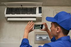 Photgraphing broken conditioner. Technician photographing installed air conditioner on smartphone Royalty Free Stock Photography