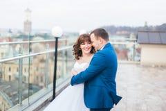 Photo émotive du marié étreignant le dos de sourire de jeune mariée tout en se tenant sur le toit Photos libres de droits