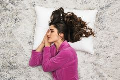 Photo from above of brunette woman wearing girlish housecoat lying and sleeping on white fur in apartment royalty free stock images