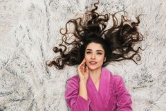 Photo from above of caucasian woman wearing girlish housecoat lying on white fur in apartment royalty free stock photos