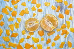 Photo from above of the peeled tangerine and many peices of orange peel. Two parts of peeled slice juicy tangerine. Royalty Free Stock Photography