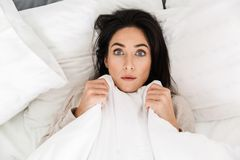 Photo from above of shocked woman 30s lying in bed at home, under white blanket. Photo from above of shocked woman 30s lying in bed at home under white blanket royalty free stock photos