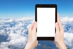 Photo of above view of white clouds in blue sky. Travel concept - tourist photograph above view of white clouds in blue sky and lands under clouds on tablet pc Stock Photo