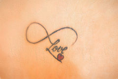Photo of abstract tattoo on skin that says love Stock Photo