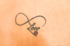 Photo of abstract tattoo on skin that says love with smal red he Stock Photography