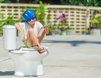 Photo absurde : garçon mignon dans les lunettes se reposant sur la toilette, qui photographie stock