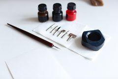 Photo of accessories for calligraphy and lettering on white tabl royalty free stock photo