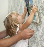 Photo accrochante de père et d'enfant sur le mur vide Image libre de droits