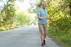 Photo of active sportsman in old age, joggs and listens music, has outdoor training during morning, feels fresh and confident, wea Stock Image