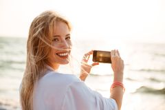 Photo of adorable blonde woman 20s smiling, and taking photo of Stock Images
