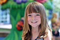 Photo of an adorable smiling young girl. 's face in outside park amusement area stock photo