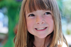 Photo of an adorable smiling young girl. 's face in outside park amusement area royalty free stock photo