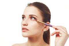 Photo of adorable woman does make up with special brush, has healthy pure skin and painted lips, being professional make up artist Stock Photo