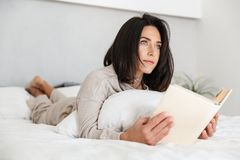 Photo of adorable woman 30s reading book, while lying in bed with white linen at home stock photography