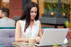 Photo of adorable young female model types something on laptop computer, prepares bussines repot. Beautiful brunette student prepa stock images