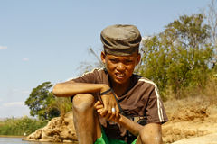 Photo of adorable young happy boy - african poor child on the ri Royalty Free Stock Images