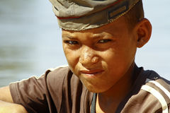 Photo of adorable young happy boy - african poor child on the ri Royalty Free Stock Photography