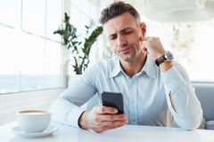 Photo of adult serious man 30s sitting alone in city cafe with c. Up of cappuccino and using black smartphone Royalty Free Stock Photos