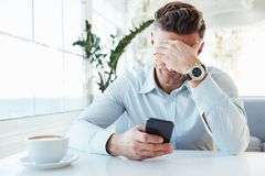 Photo of adult upset man 30s sitting alone in city cafe with cup. Of cappuccino and propping up his head with hand while using black smartphone Stock Photography