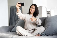 Photo of adult woman 30s taking selfie on cell phone, while sitting on couch in bright apartment royalty free stock photos