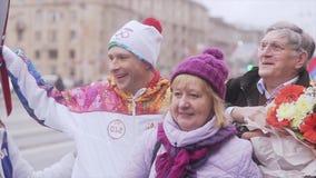 Photo adulte volontaire de personnes avec le porteur de flambeau Course de relais de flamme olympique de Sotchi dans le St Peters banque de vidéos