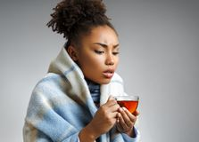 Photo of african american woman with hot tea and handkerchief. Woman is sick. Photo of african american woman with hot tea and handkerchief, wrapped in plaid on stock images