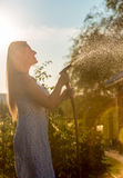 Photo against sky of woman watering garden with hose at sunny da Stock Photos