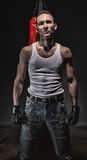Photo of aggressive man and red boxing bag. On dark backgroind Royalty Free Stock Photos