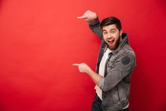 Photo of agitated man wih beard in casual clothing pointing fing. Ers on copyspace text or product with surprise and smile over red background stock photo