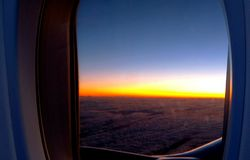 Photo of Airplane Window With View of Clouds and Golden Hour stock photo