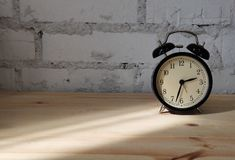 Photo of alarm clock on wooden table against background of brick wall. In room stock photography