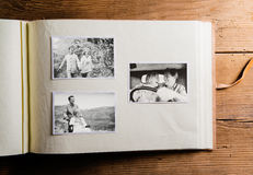 Photo album with black-and-white pictures of senior couple. Photo album with black-and-white pictures of senior couple in love. Studio shot on wooden background stock photos