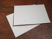 Photo Album With Blank Sheets. Old decorative photo album, with two sheets of blank white paper laying on the cover Royalty Free Stock Images