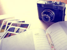 Photo album close up with an old camera and photos, filtered. Photo Royalty Free Stock Photography