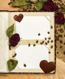 Photo album and dry red roses on coffee seeds Royalty Free Stock Image