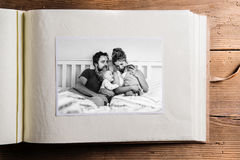 Photo album with picture of young family. Fathers day. Photo album with black-and-white picture of young parents at home sitting in bed with their cute son and Royalty Free Stock Photo
