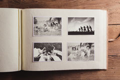 Photo album with pictures. Photo album with black and white family pictures. Studio shot on wooden background Royalty Free Stock Photos