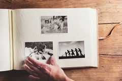 Photo album with pictures. Photo album with black and white family pictures. Studio shot on wooden background Royalty Free Stock Photography