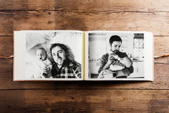 Photo album with pictures of father and baby son. Fathers day. Photo album with pictures of young father and his cute newborn baby son. Fathers day concept Royalty Free Stock Photos