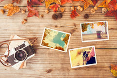 Photo album in remembrance and nostalgia in autumn fall season on wood table. Instant photo of retro camera - vintage and retro style Stock Photos