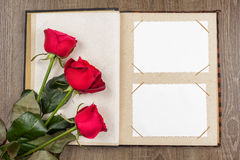 Photo album and roses on wood Royalty Free Stock Photography