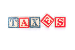 Photo of a alphabet blocks spelling TAXES isolate on white background Stock Images